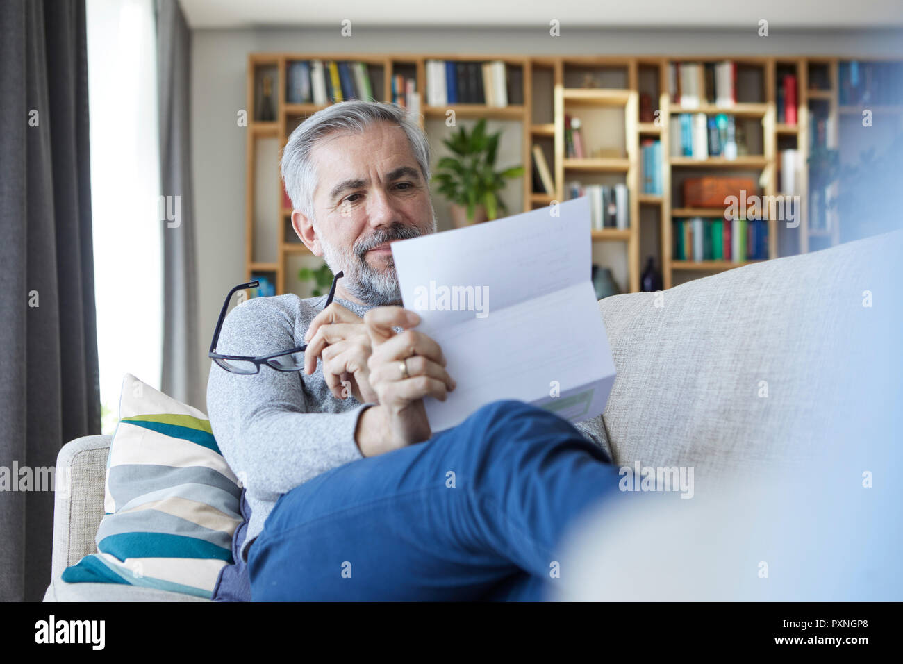Mature man sitting on couch at home reading letter - Stock Image