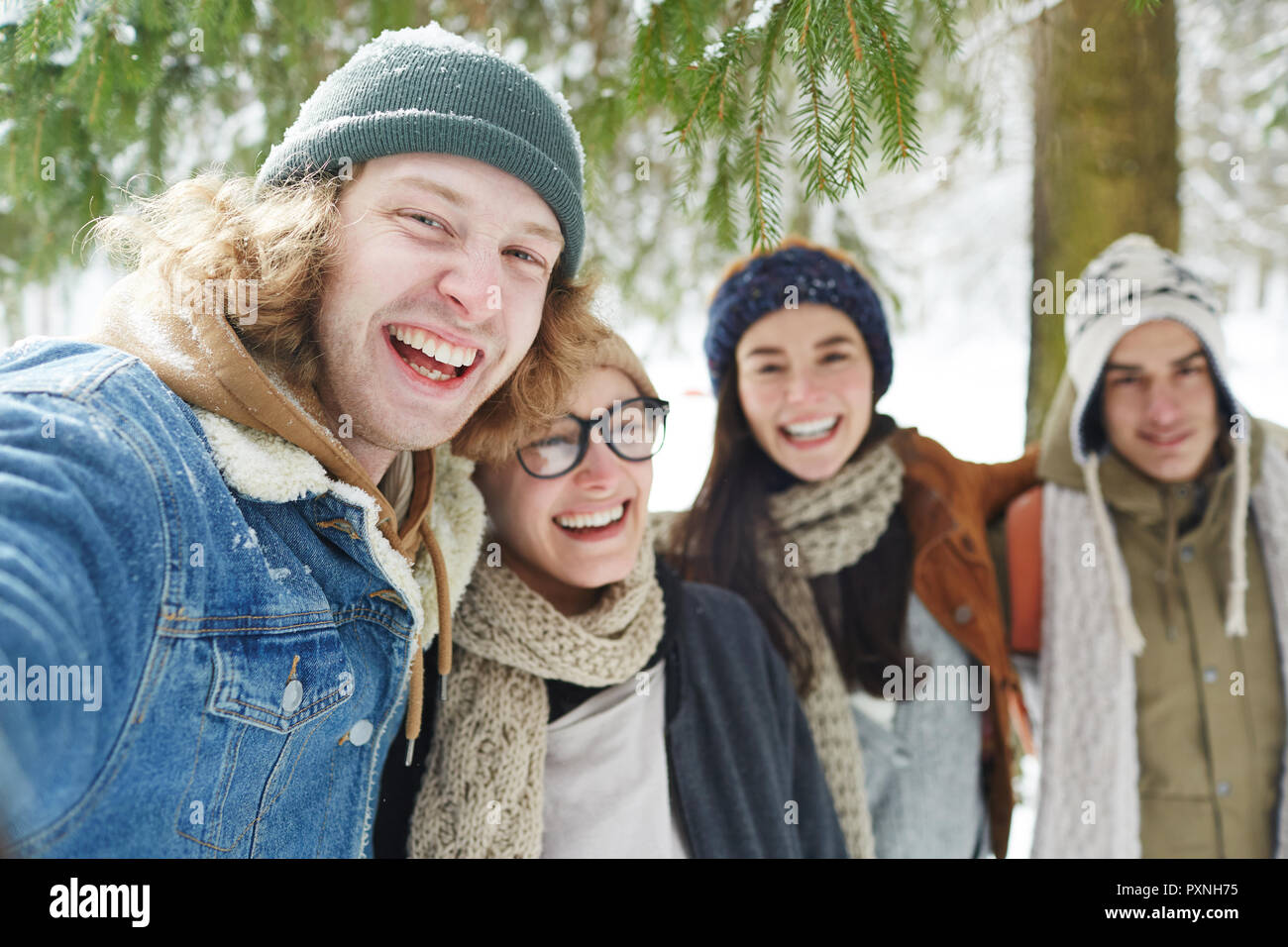 Portrait of four happy young people enjoying time in winter resort and laughing merrily looking at camera, focus on man in front - Stock Image