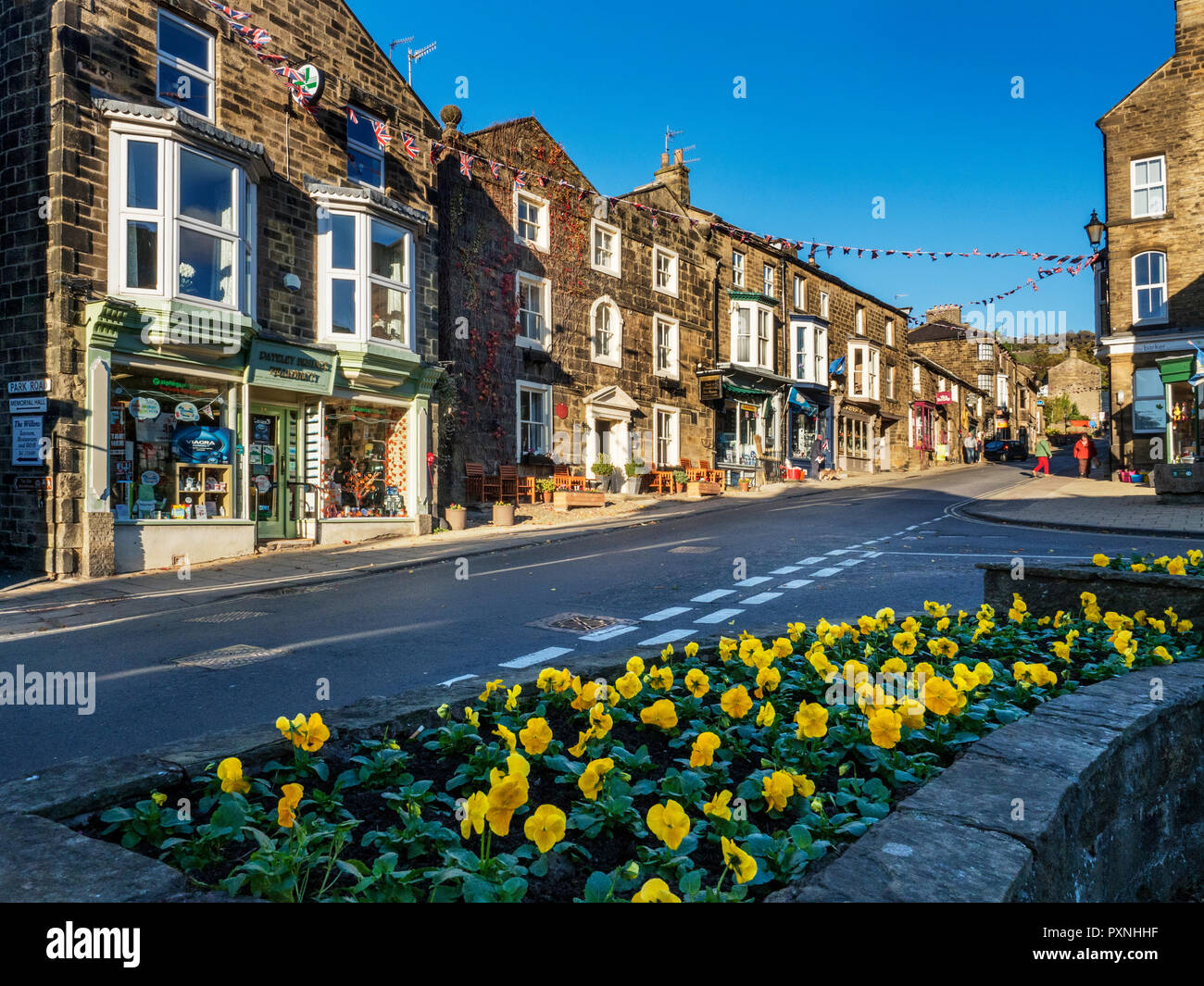 Winter pansies in flower and shops on the High Street at Pateley Bridge North Yorkshire England - Stock Image