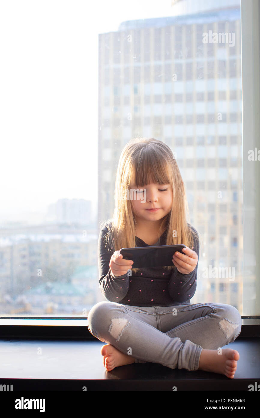 Cute little at home in white room is sitting near window. Stock Photo