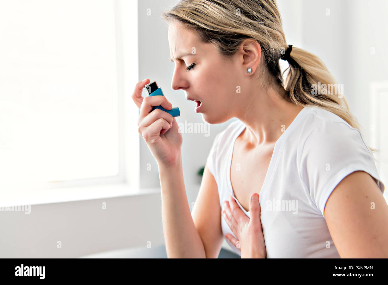 An Asthmatic using her inhaler because of breath difficulties - Stock Image