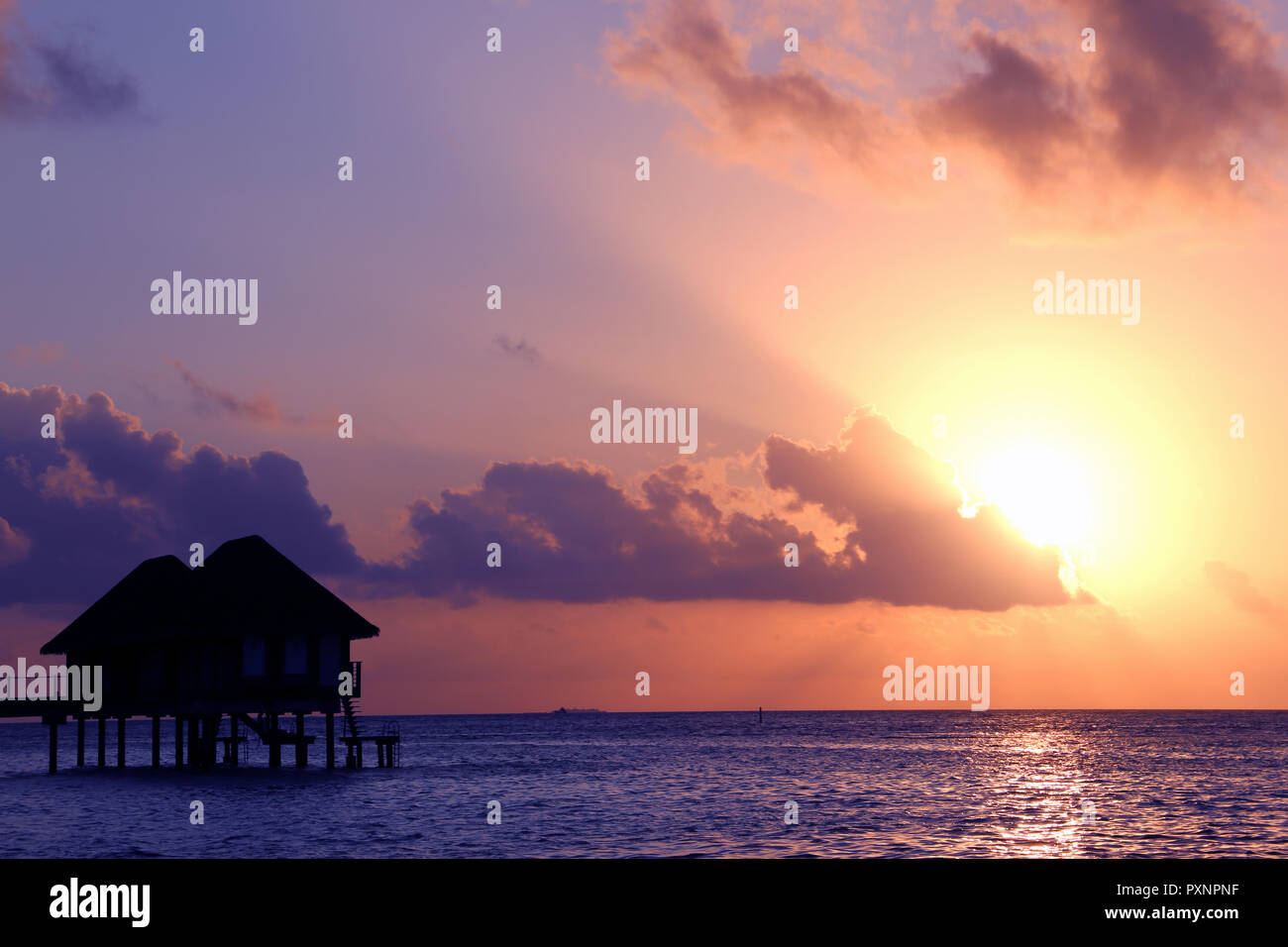 Over-water bungalow at sunset - Stock Image