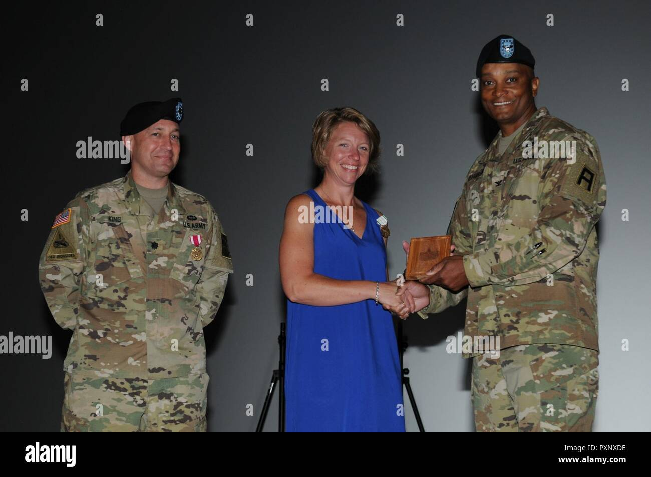 Col. Flint Patterson, commander of the 4th Cavalry Multi-Functional Training Brigade, awards Ms. Tina King and Lt. Col. Steven King, the outgoing commander of the 3rd Battalion, 337th Regiment, a gift from the 4th Cavalry MFTB for their service. The Kings served as leaders of the 3-337th family readiness group from June 6, 2015, to June 4, 2017. - Stock Image