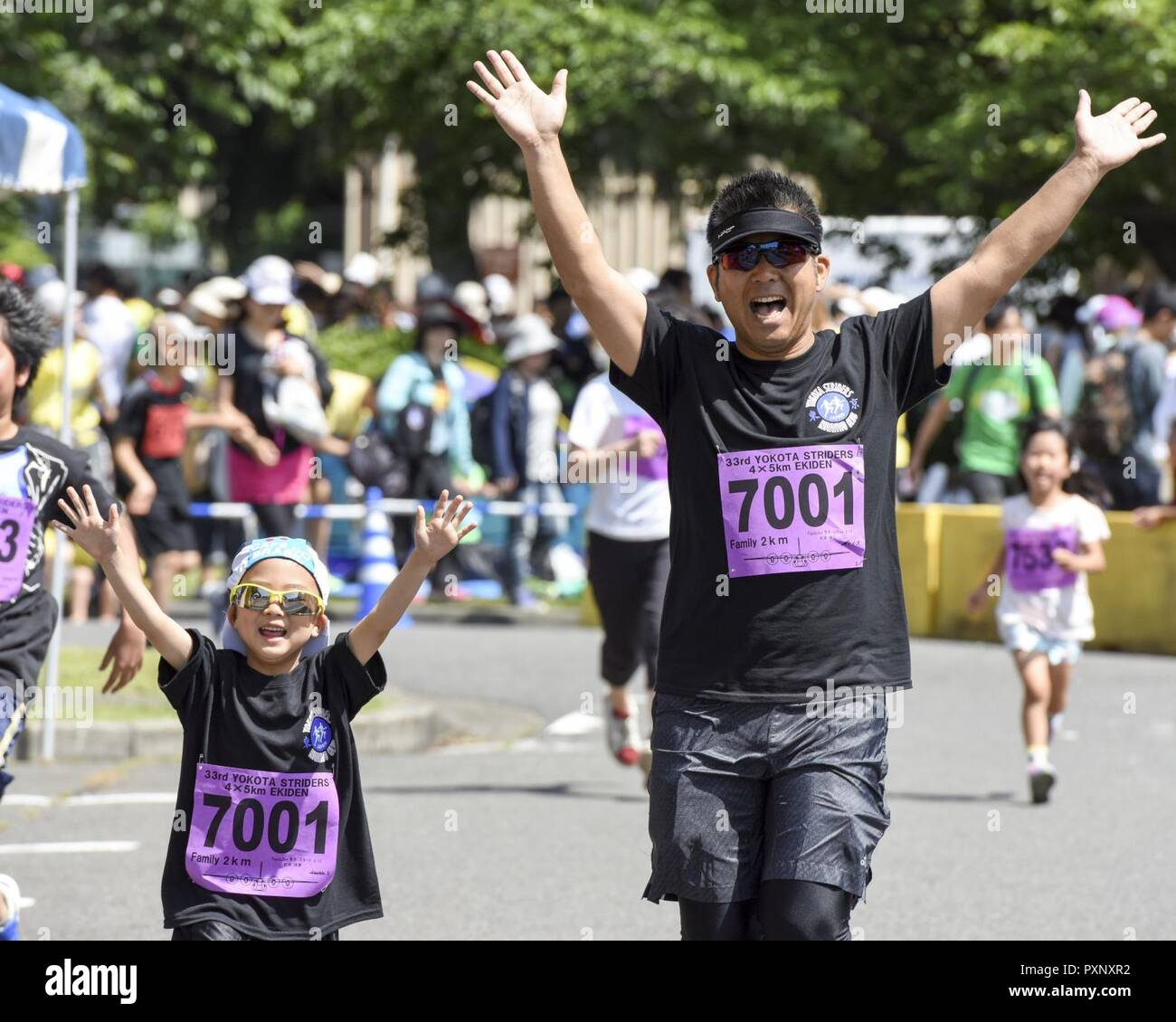 A father and daughter cross the finish line together with their hands up at the 2K Family Run during the 33rd Annual Yokota Striders Ekiden at Yokota Air Base, Japan, June 4, 2017. More than 5,000 runners participated in the event hosted by the Yokota Striders Running Club. - Stock Image