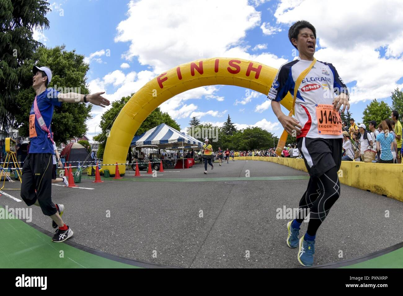 Participants in the Ekiden Race cross the finish line at Yokota Air Base, Japan, June 4, 2017. More than 5,000 runners participated in the event hosted by the Yokota Striders Running Club. - Stock Image