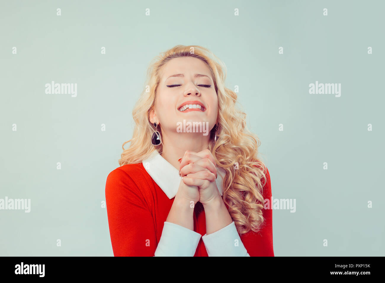 Beautiful woman pleading with hands together - Stock Image