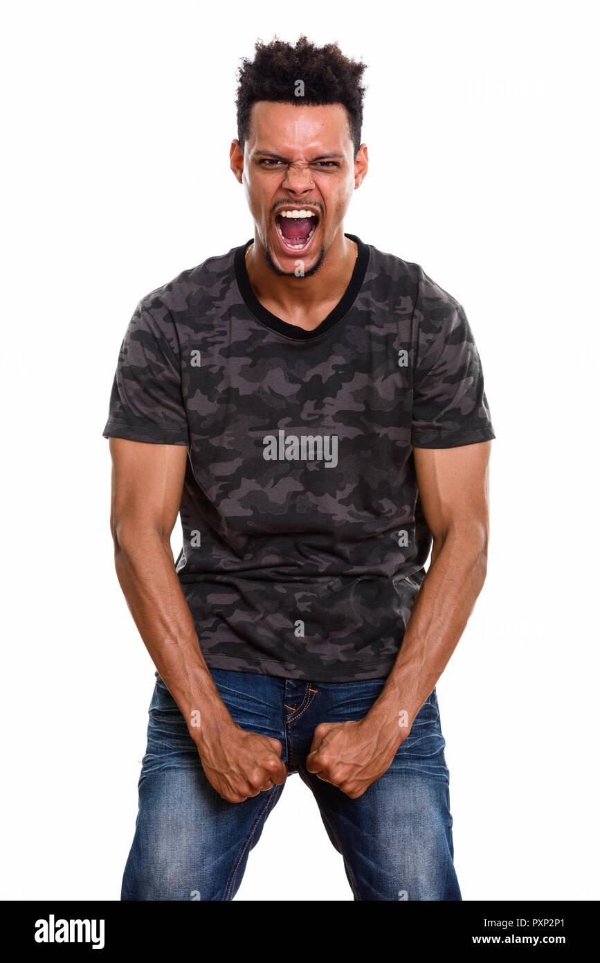 Studio shot of young African man looking furious  - Stock Image