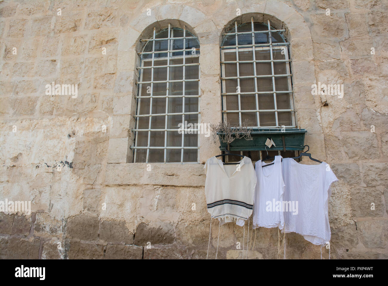 Jewish prayer clothing, Tallit Katans hanging out to dry next to a window in the old town of Jerusalem. - Stock Image