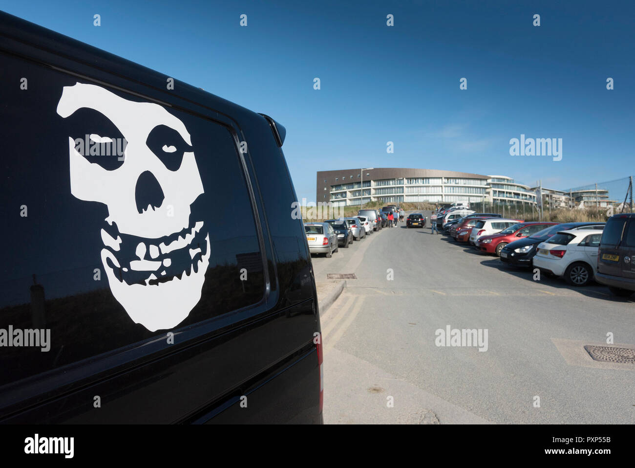 A white skull motif artwork on the side of a black van in the car park at Fistral in Newquay in Cornwall. - Stock Image