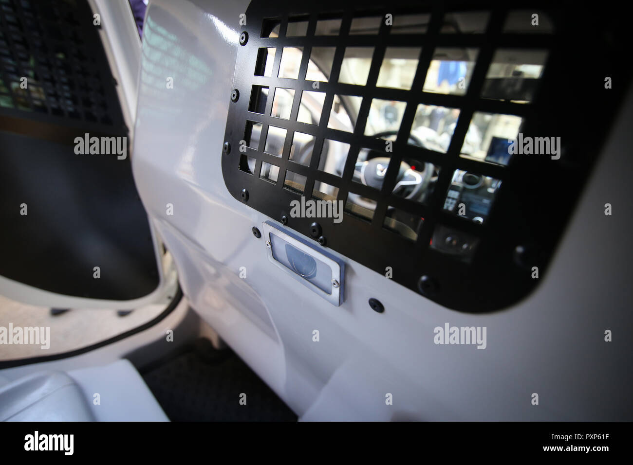 Details from the interior of a Romanian police vehicle, with bars on windows and a monitoring video camera in the back - Stock Image