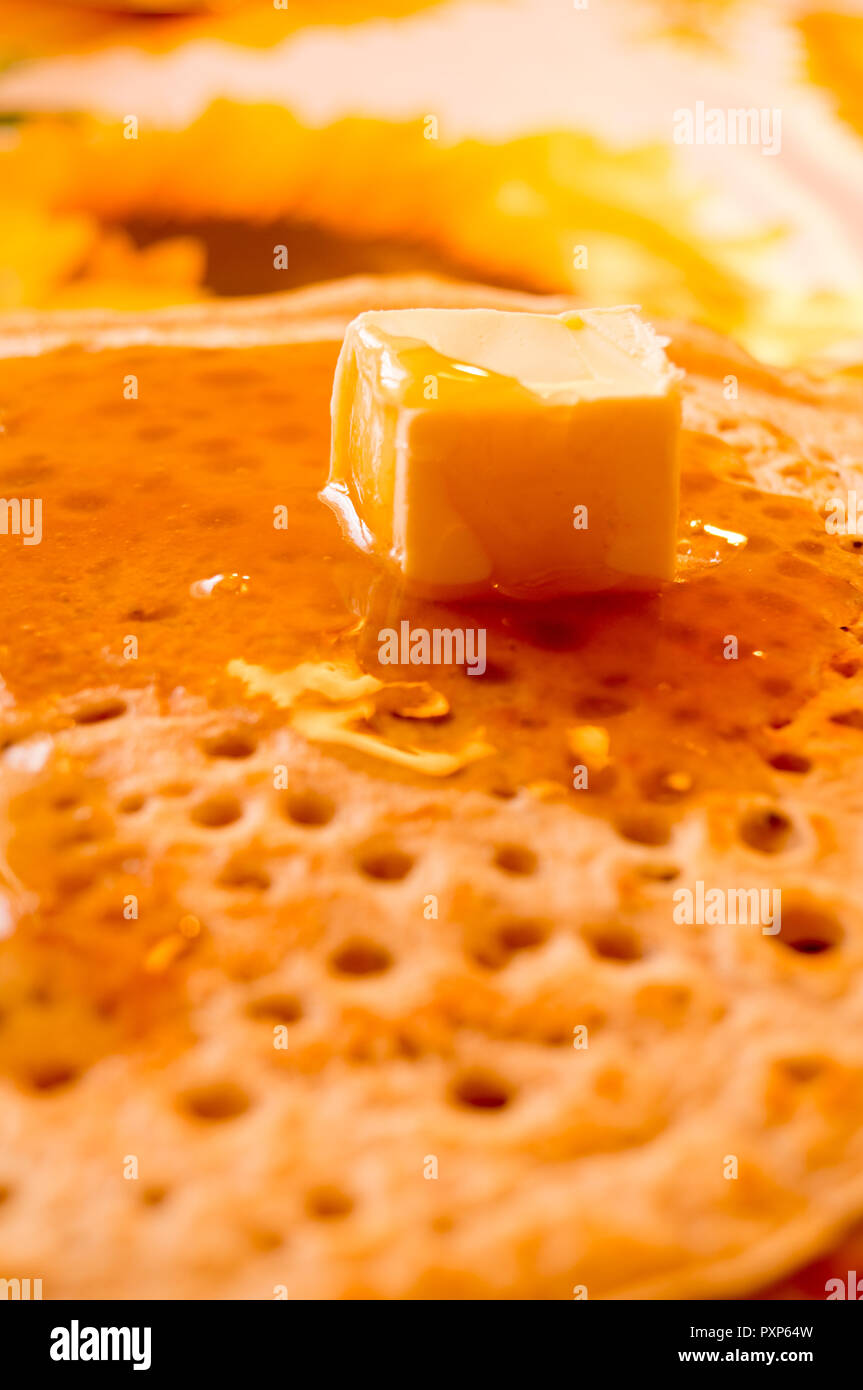 Pancakes. Honey. Butter. Maslenitsa. Delicious freshly-fried rumpy pancake is poured with liquid home-made honey and butter - Stock Image