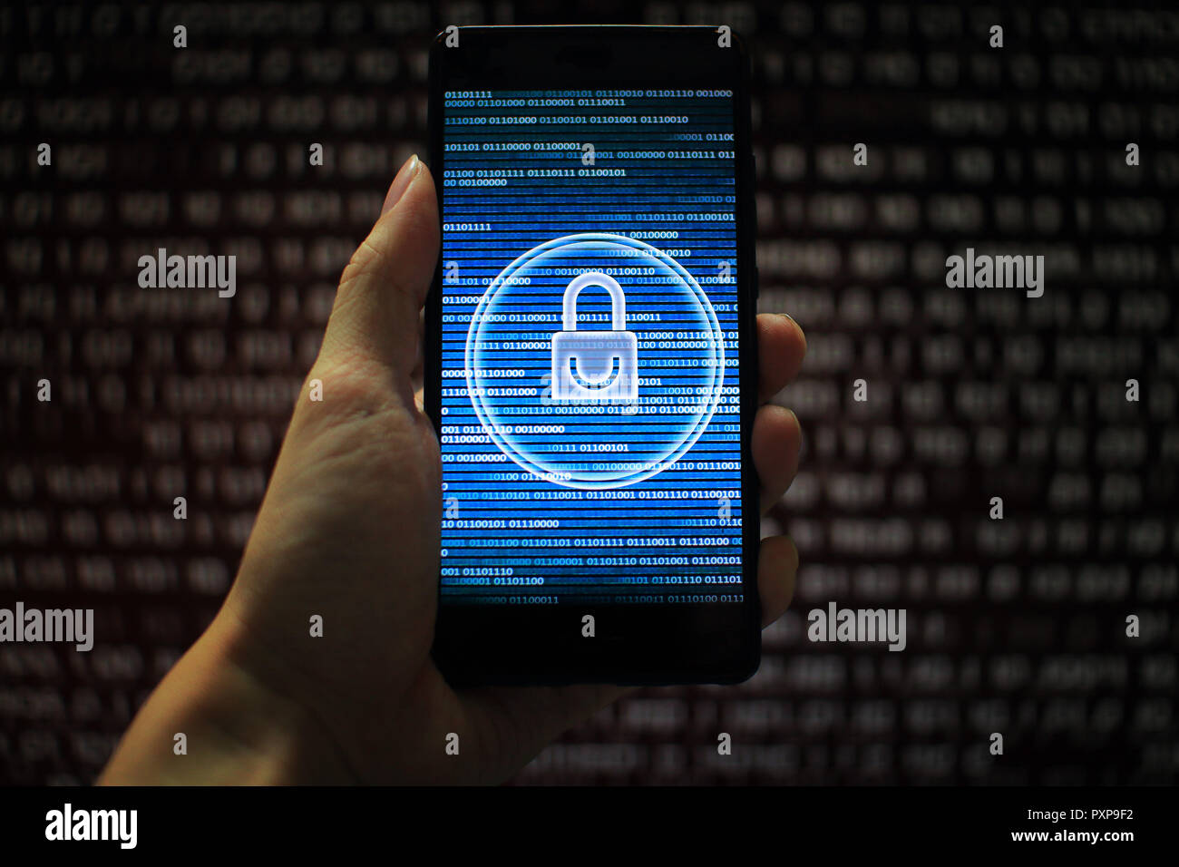 system integrity working while other pass down. hand holding mobile phone with padlock icon on blue binary code screen. Error message in computer. - Stock Image