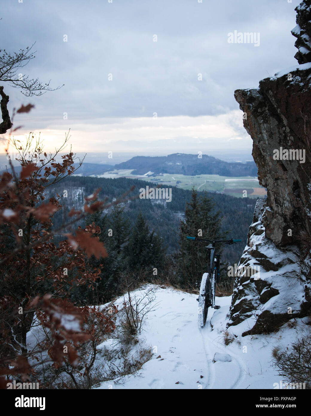 trail covered by snow and a mountain bike. in front of winter landscape on a mountain under a rock. focus on mtb. Black Forest, Germany - Stock Image