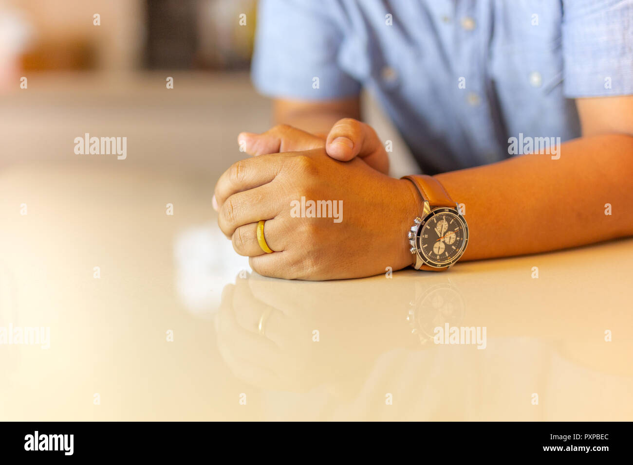 Man's left hand with gold wedding ring on his finger on marble table. - Stock Image