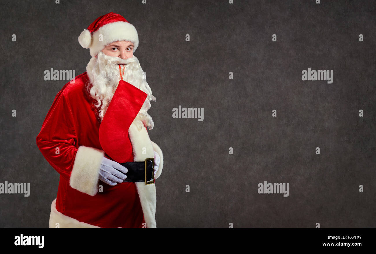 Happy funny Santa Claus with red sock on background. - Stock Image