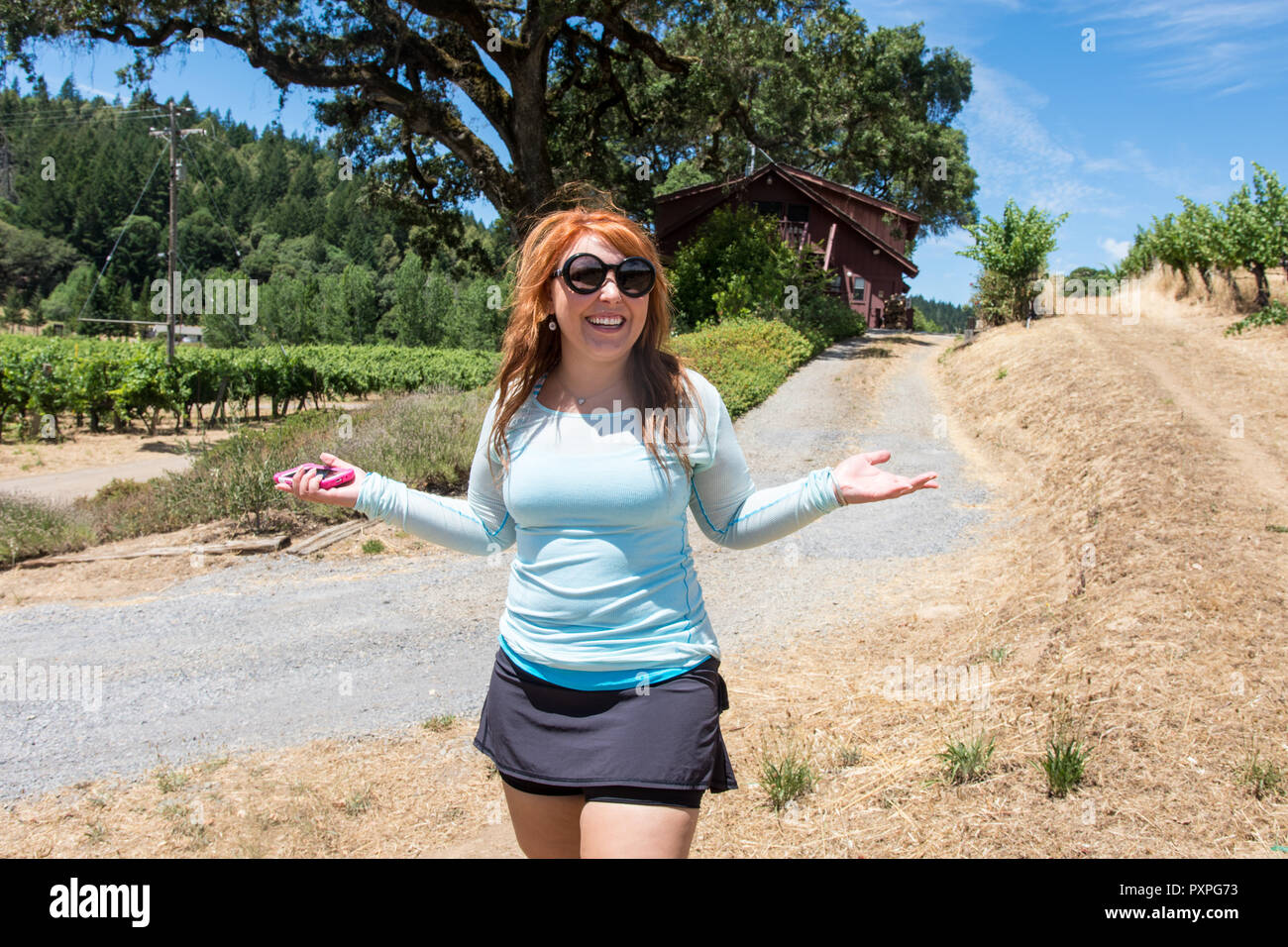 Red headed ginger adult female (20s) millennial holds out her arms in happiness while walking on a dirt trail. Smiling and happy, holding generic smar - Stock Image