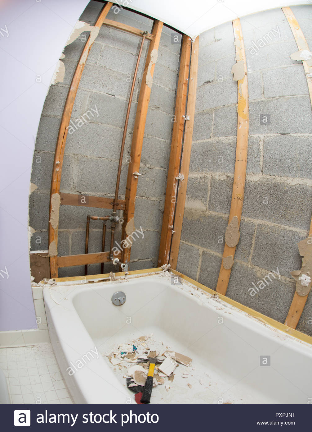 Location shot of a bathtub and shower being demolished - Stock Image