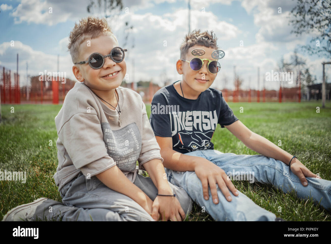 Close up of boys sitting in the park on green grass. Happy family concept. - Stock Image