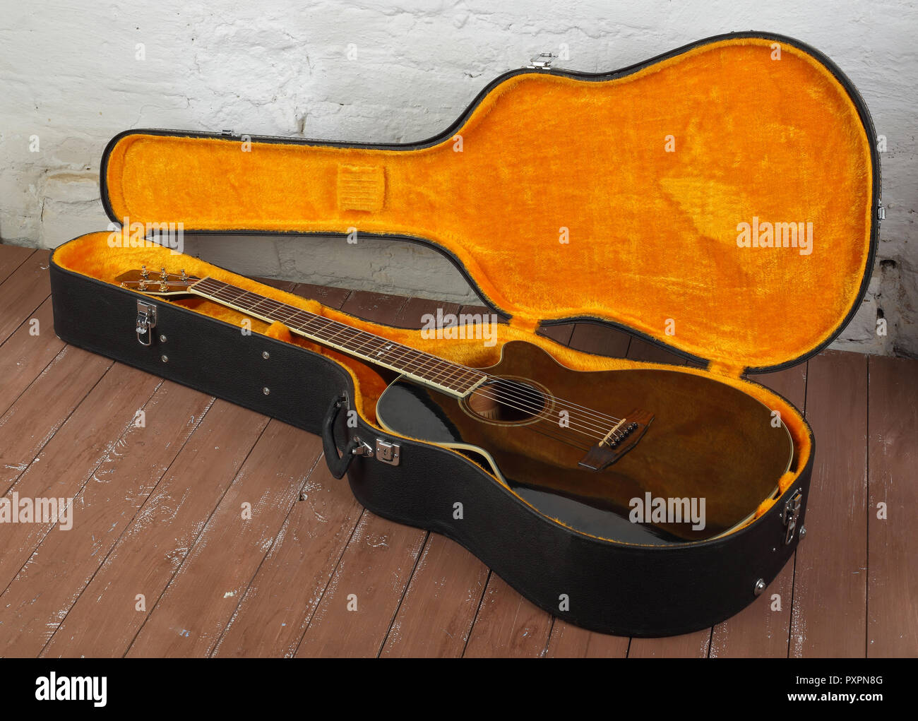 Musical instrument - brown cutaway acoustic guitar in hard case on a wood background. Stock Photo