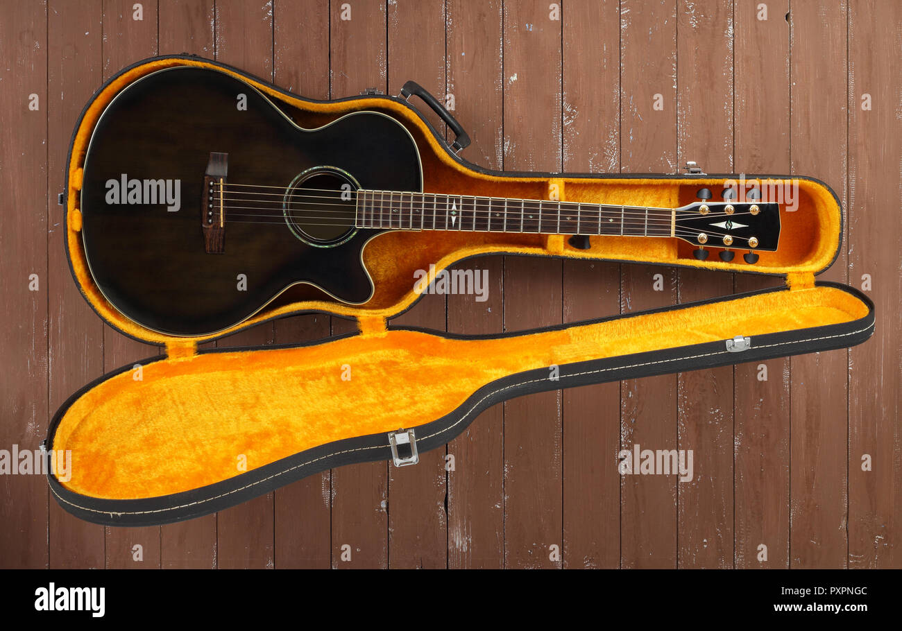 Musical instrument - Top view brown cutaway acoustic guitar in hard case on a wood background. Stock Photo