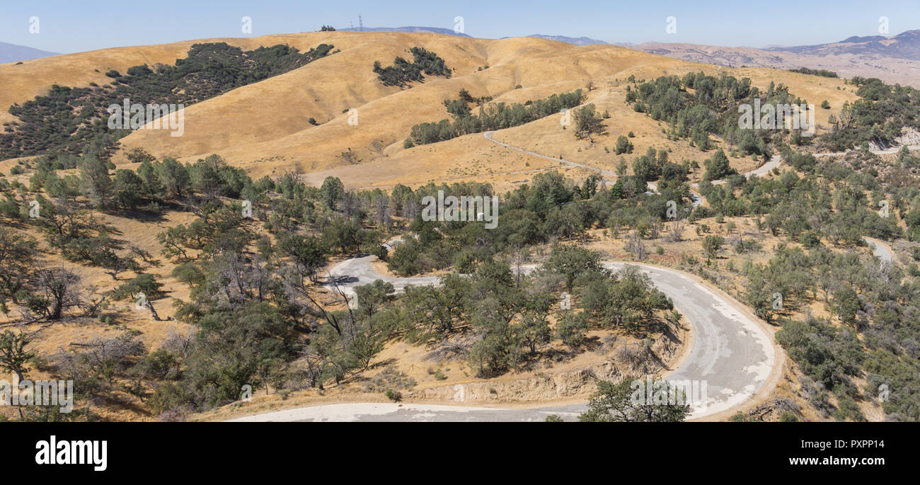 Winding asphalt road leads through the woods and hills of southern California outside Los Angeles. - Stock Image
