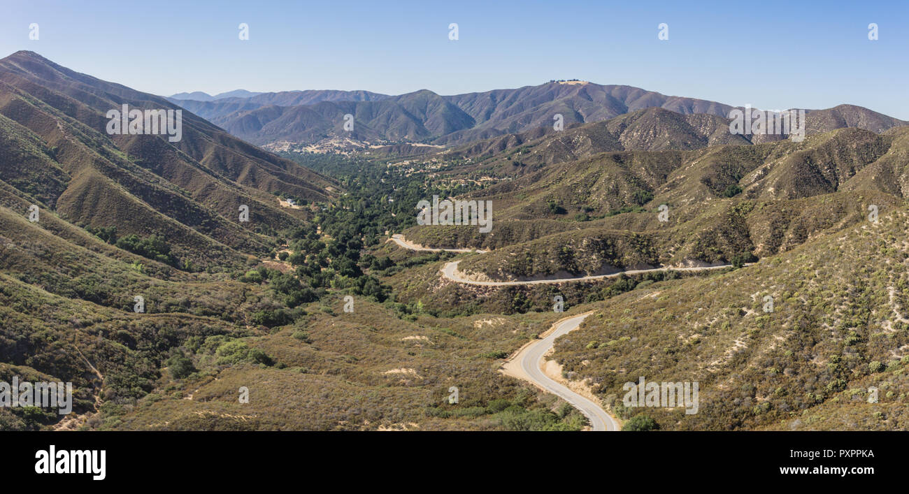 Single road winds into a mountain valley in the hills of southern California's Angeles National Forest. - Stock Image