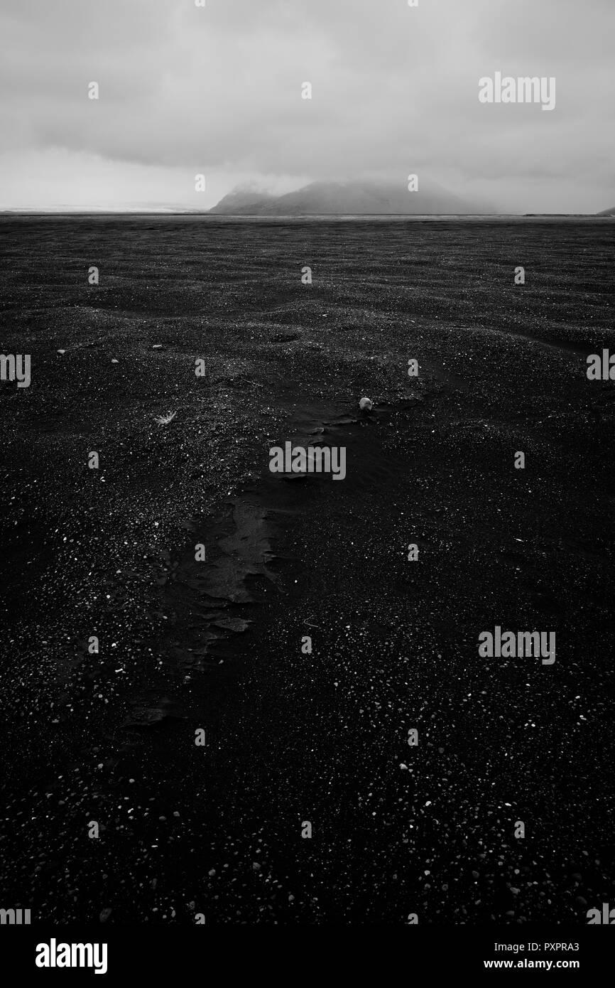 The empty black basalt sand glacial plain landscape of south Iceland. - Stock Image