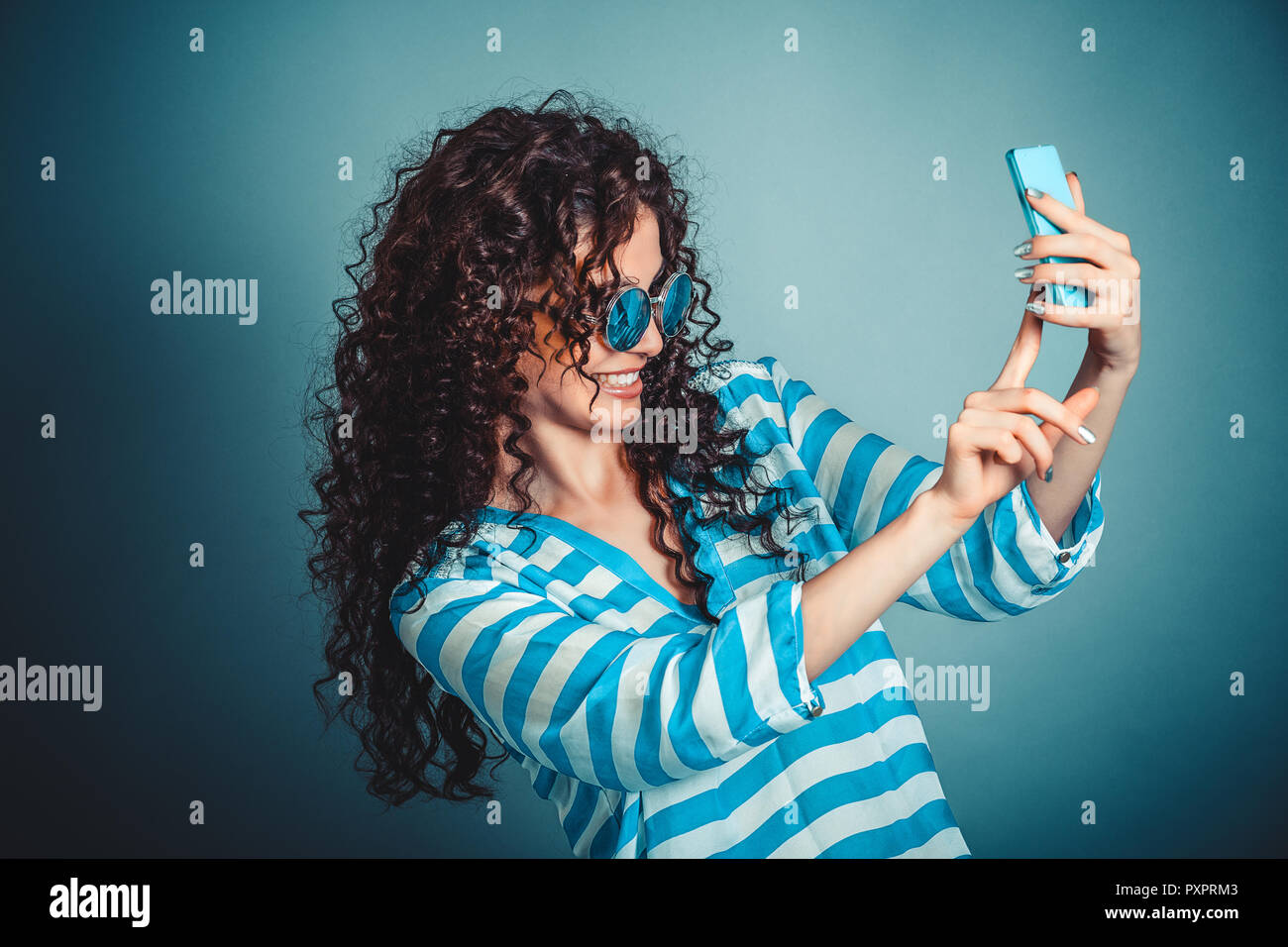 Woman making selfie with smartphone isloated on blue background - Stock Image
