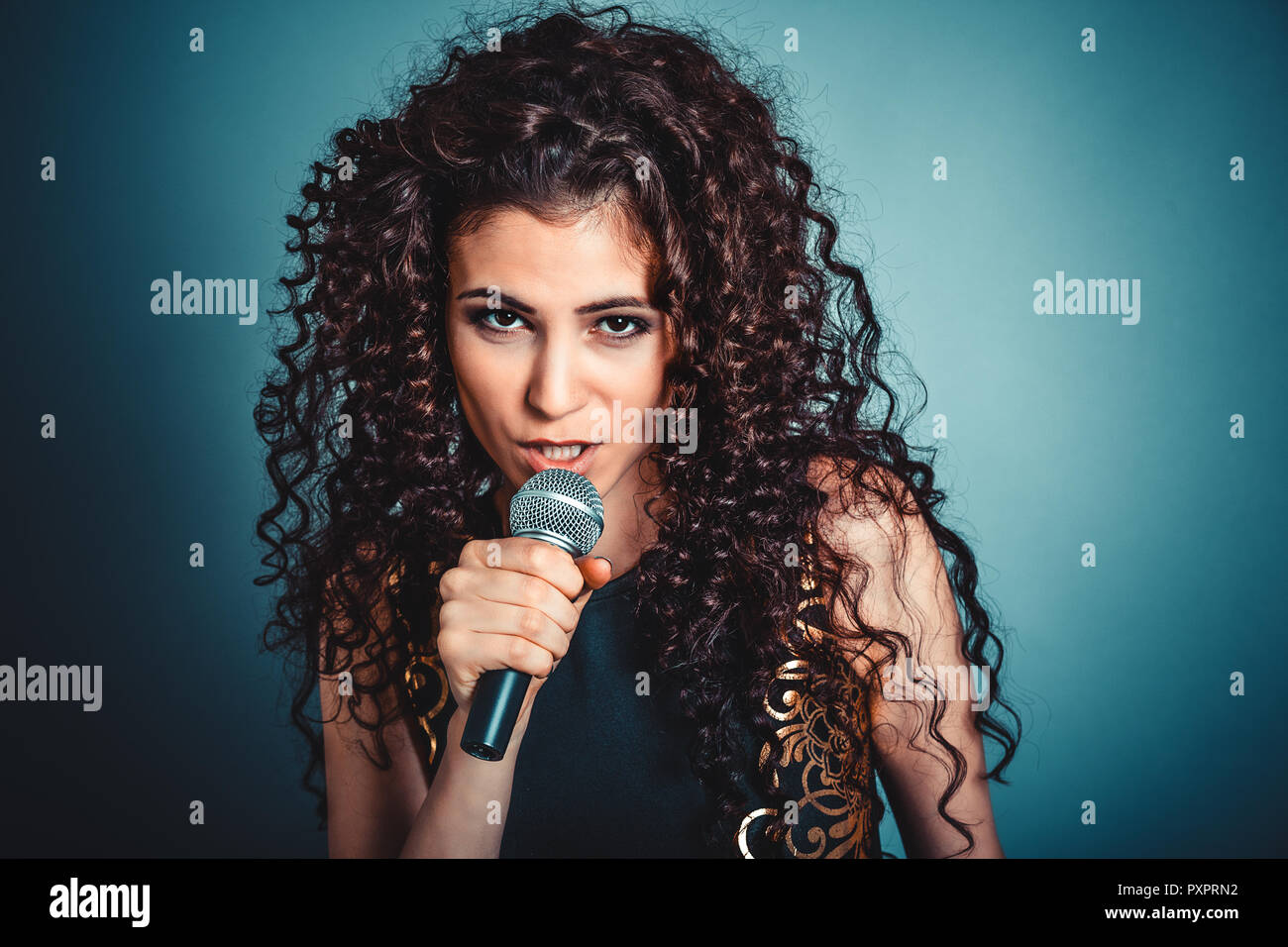 Woman unhappy talking by microphone looking skeptical to you - Stock Image