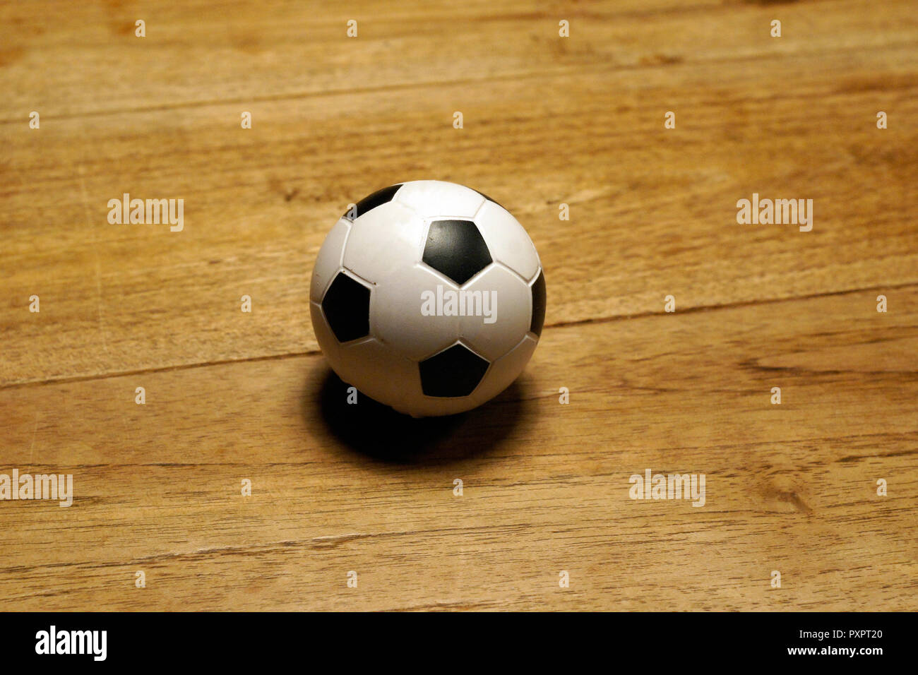 white and black mini football at wooden table - Stock Image