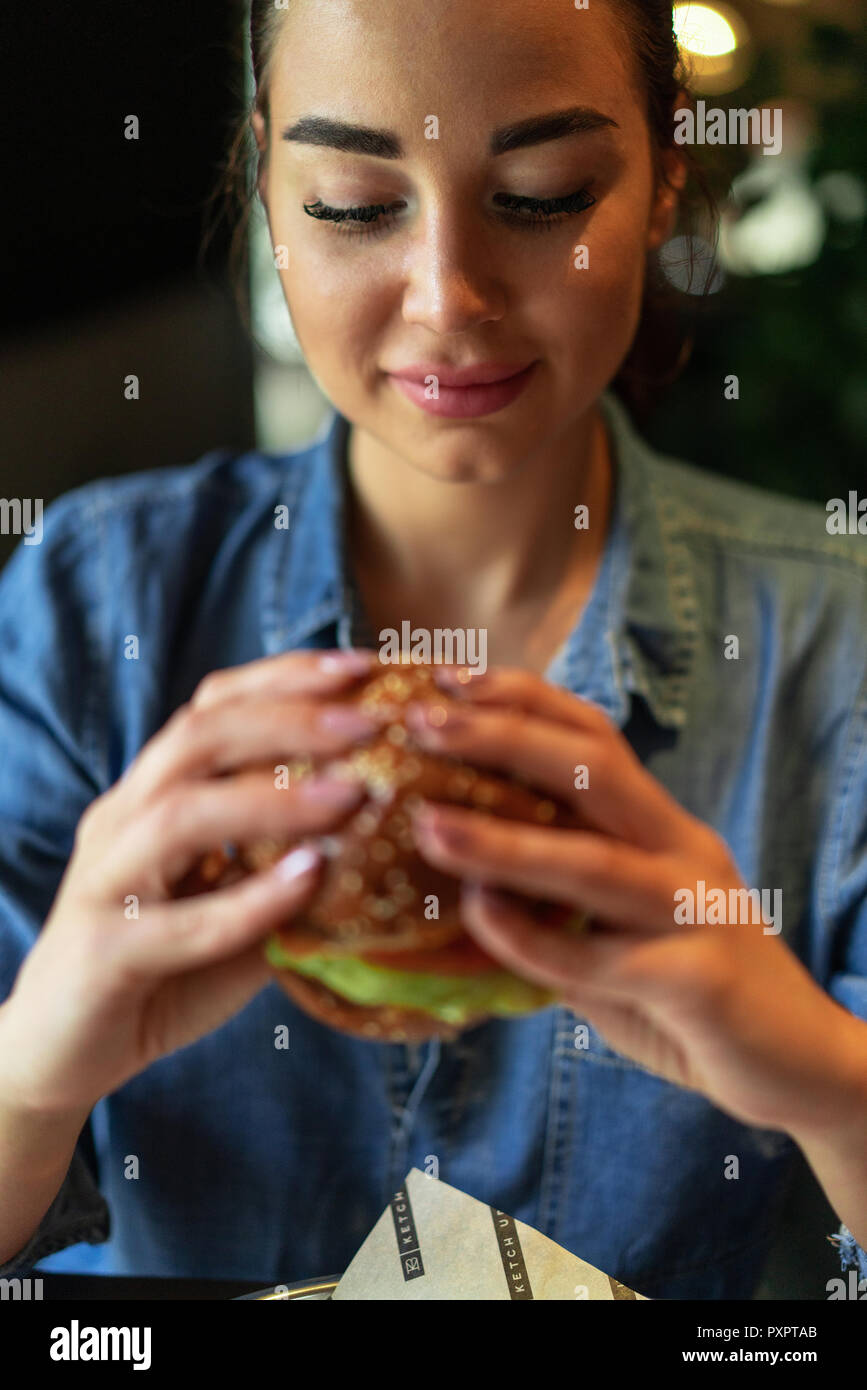 Young attractive brunette woman holding juicy burger. - Stock Image