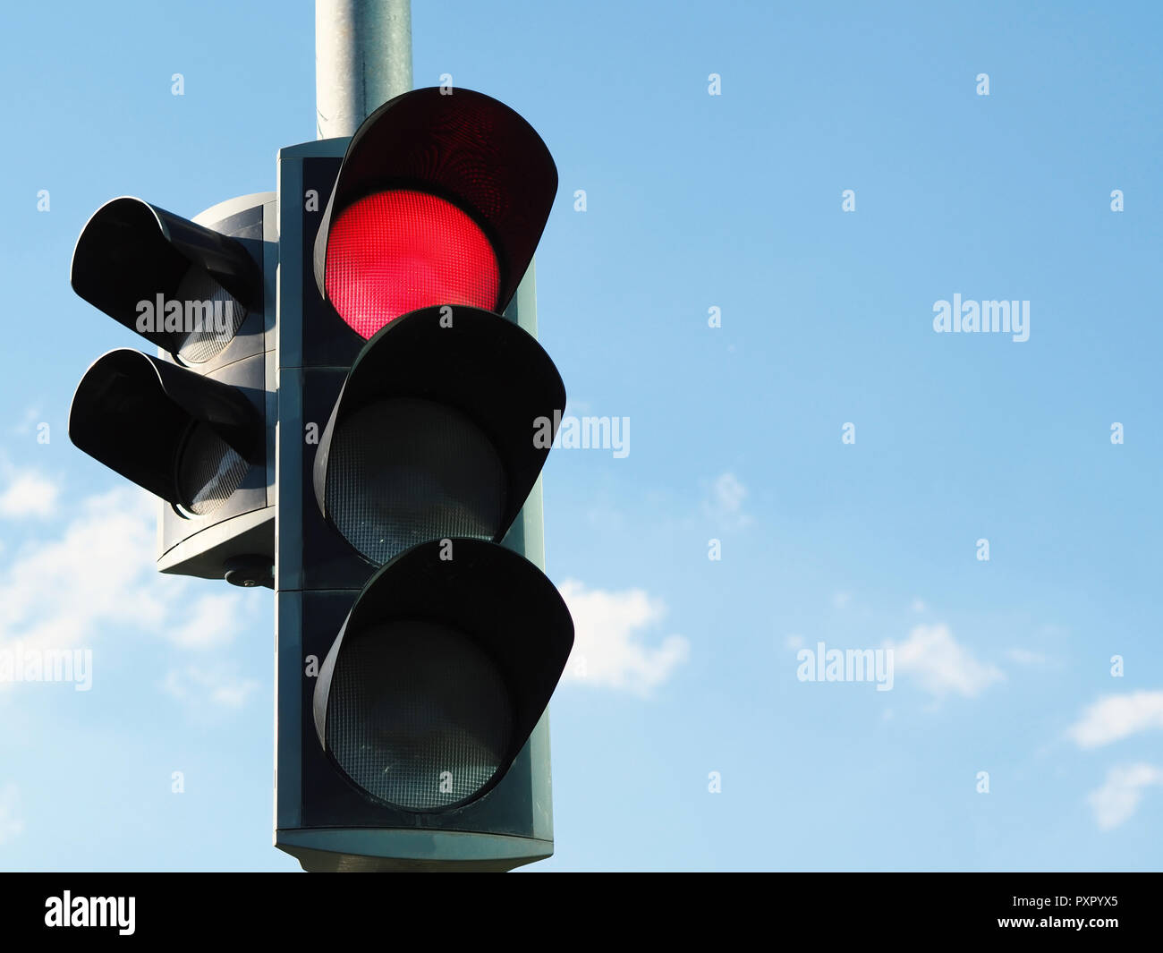 traffic light with red light and blue sky in background. Stock Photo