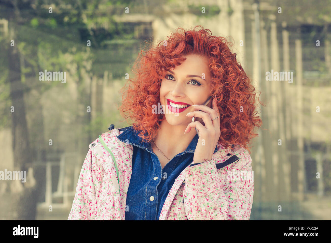 curly redhead woman outdoors talking by mobile phone - Stock Image