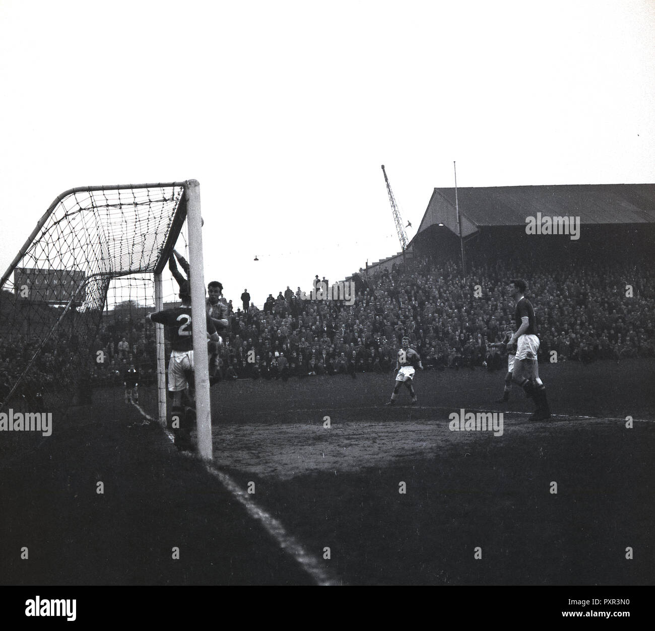 1950s, historical, goalmouth action at a football match taking place at the Old Den, New Cross, London SE14, the home of Millwall FC, established in 1885. The large ground which opened in 1910 and while in use was known as 'The Den', could take 47,000 spectators, with over 43,000 of these standing. - Stock Image