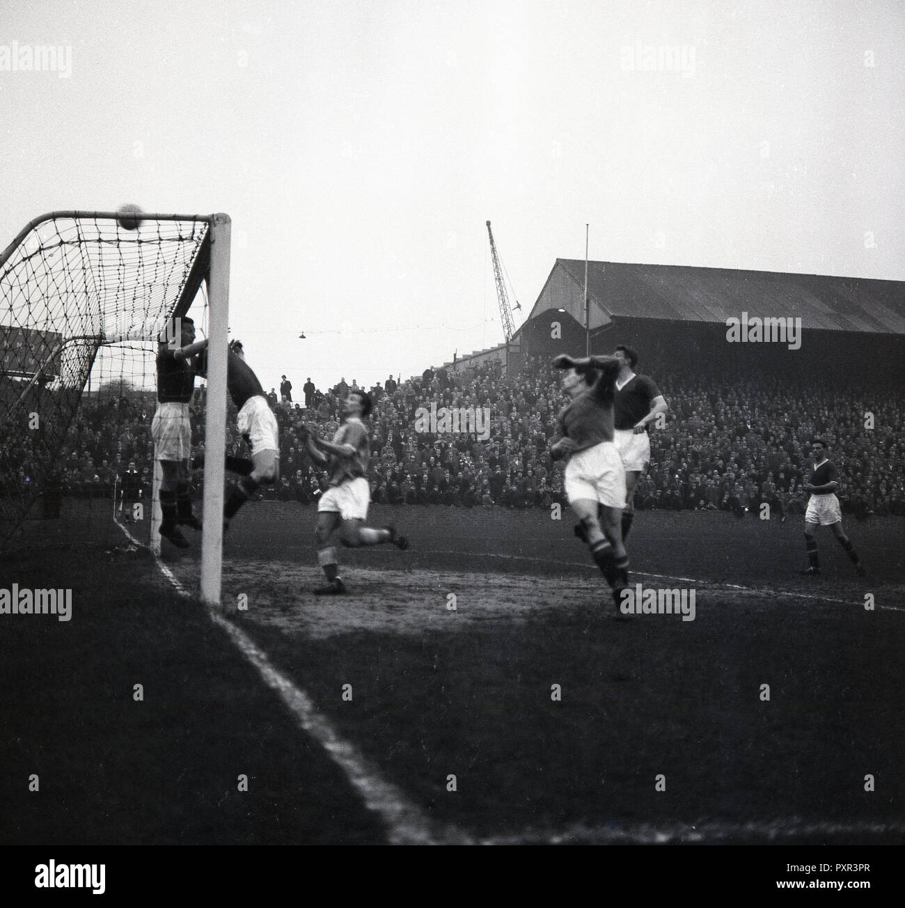 1950s, historical, goal line action at a football match at the Old Den, New Cross, London SE14, the home of Millwall FC, established in 1885. The large ground which opened in 1910 and while in use was known as 'The Den', could take 47,000 spectators, with over 43,000 of these standing. - Stock Image