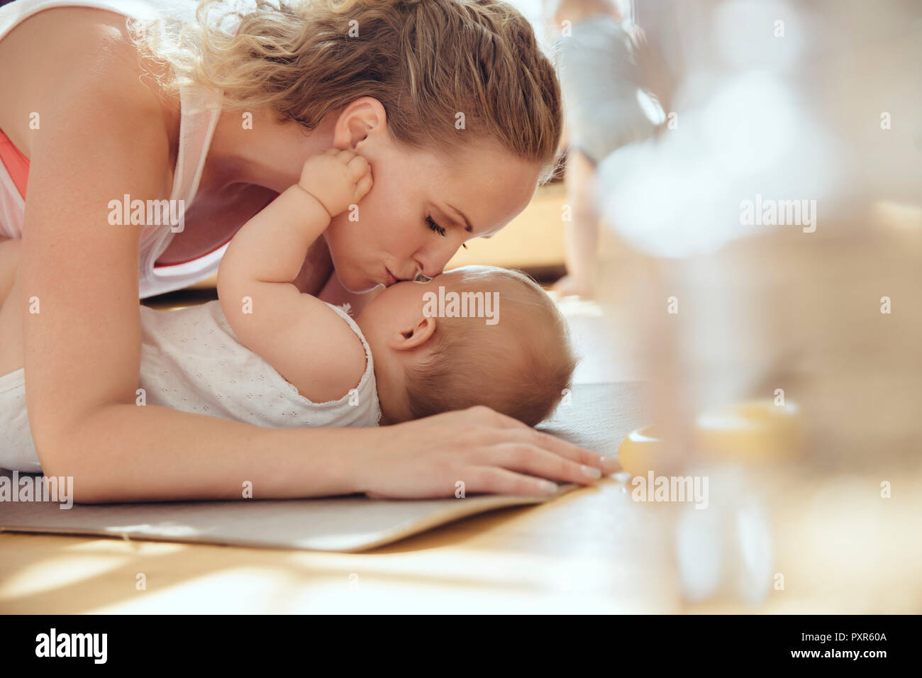 Mother kissing her baby while working out on a yoga mat Stock Photo