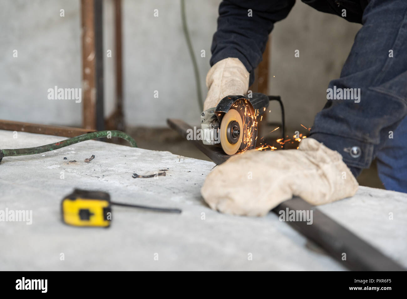 Metal cutting process with disc grinder. Hobby and work at home workshop. People at work, skills and abilities - Stock Image