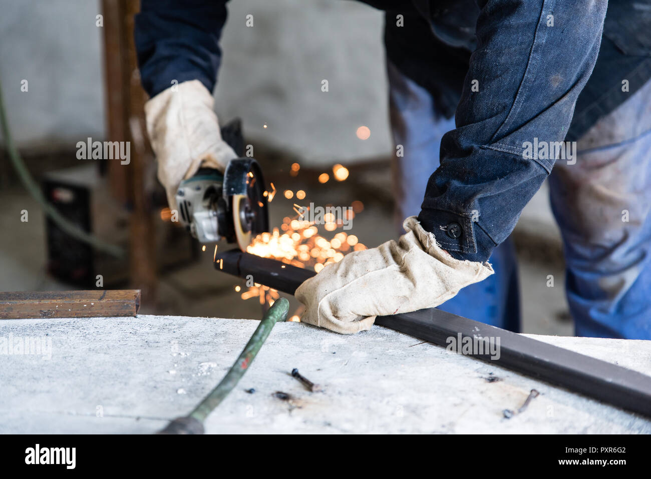 Work at home workshop. Man cuts the metal profile with electric angle grinder, skills and abilities - Stock Image