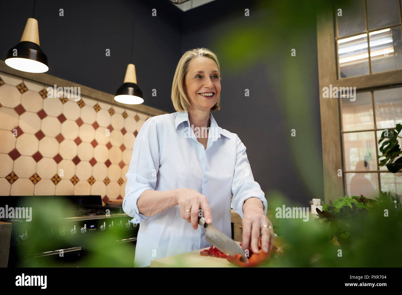 Smiling mature woman chopping bell pepper in kitchen - Stock Image