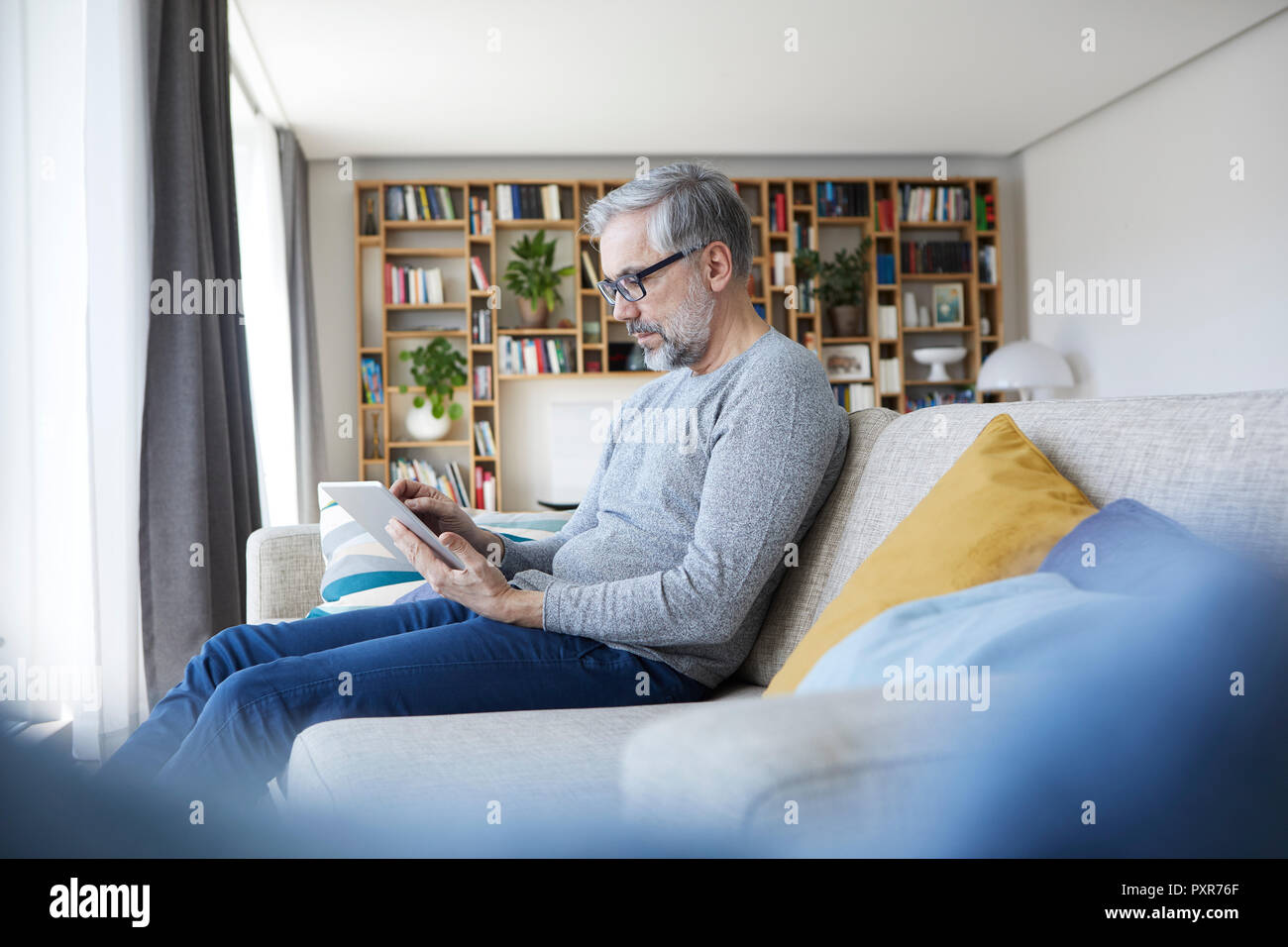 Mature man sitting on couch at his living room using tablet - Stock Image