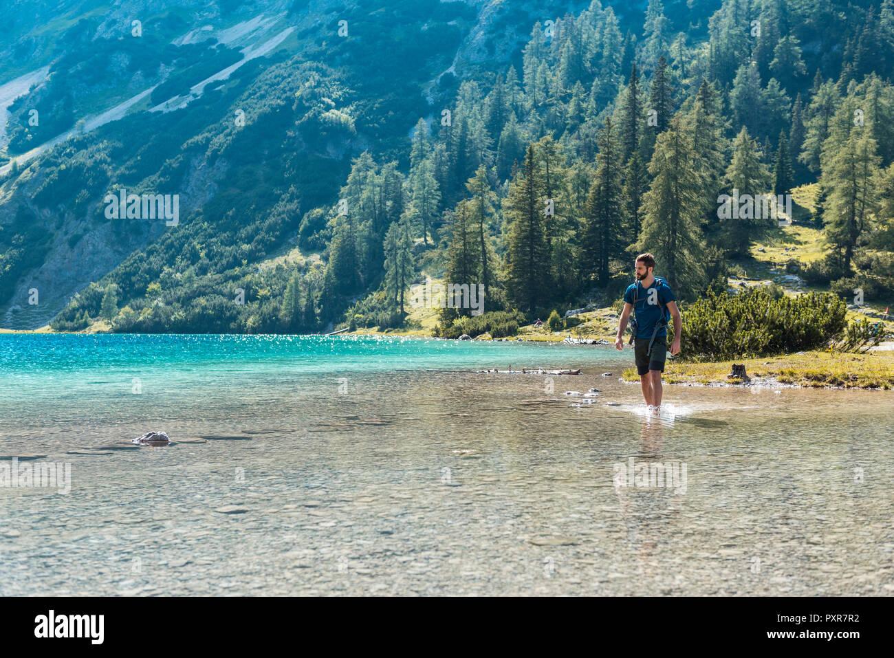 Austria, Tyrol, Hiker at Lake Seebensee walking ankle deep in water - Stock Image