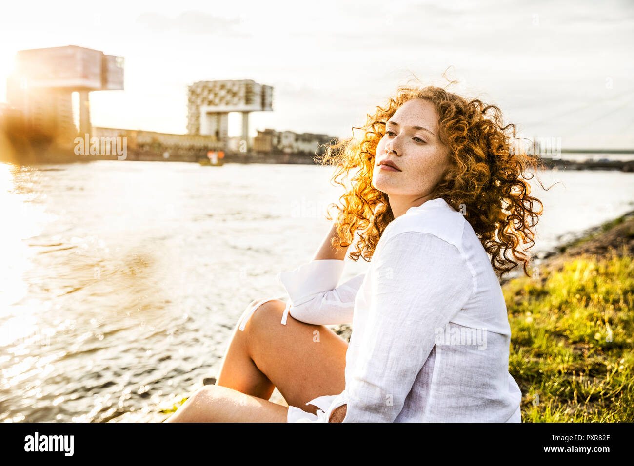 Germany, Cologne, portrait of young woman sitting at riverside in the evening - Stock Image