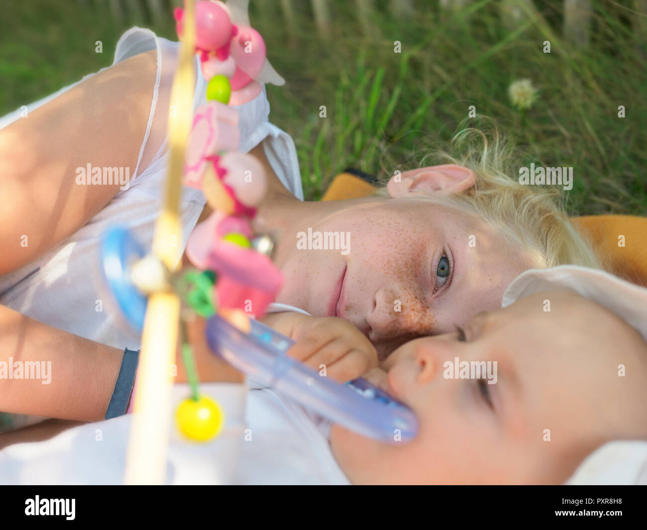 Freckled girl lying with baby girl on blanket on a meadow - Stock Image