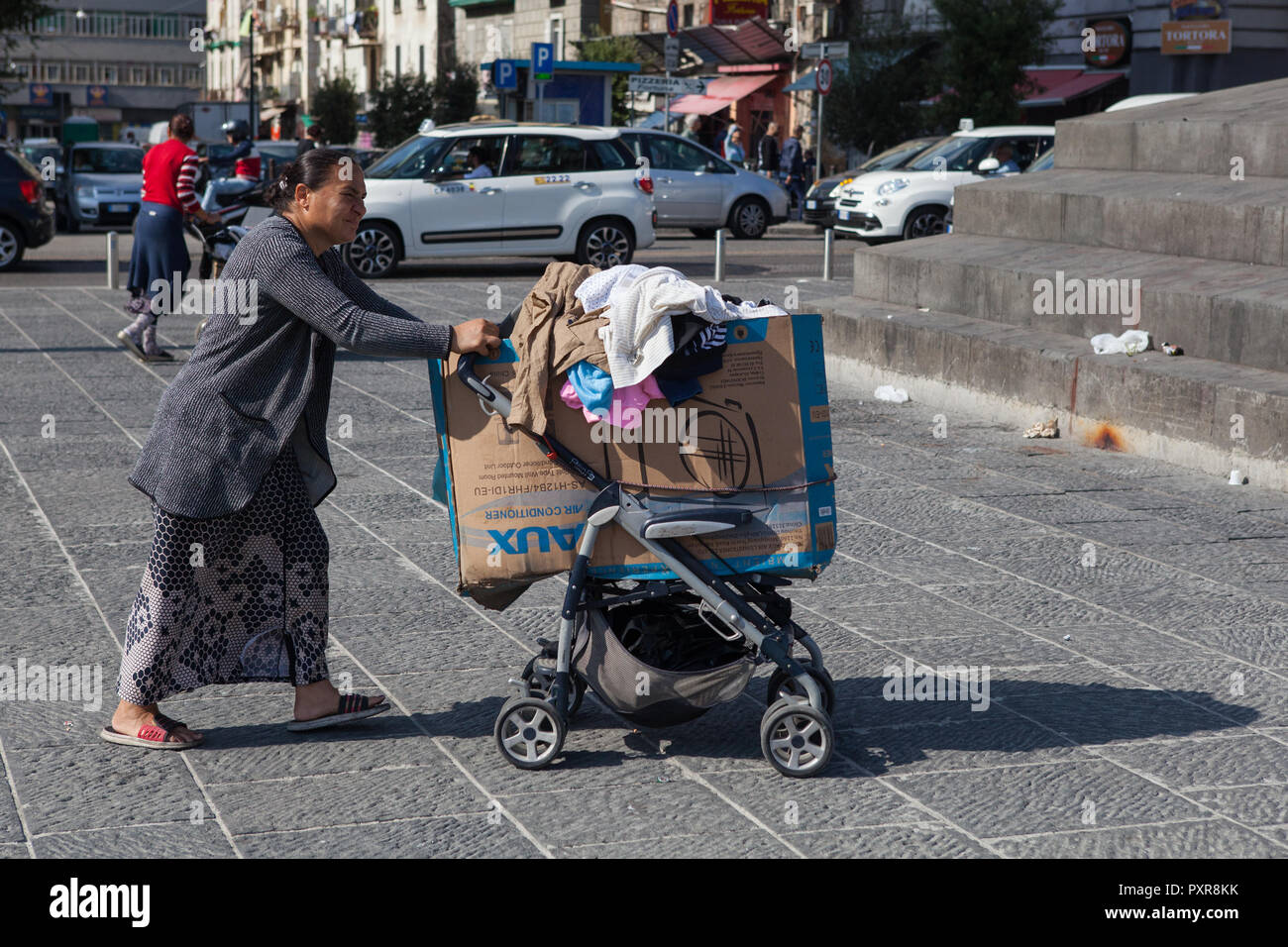 A homeless migrant pushes her belongings through the streets of Naples, Italy - Stock Image