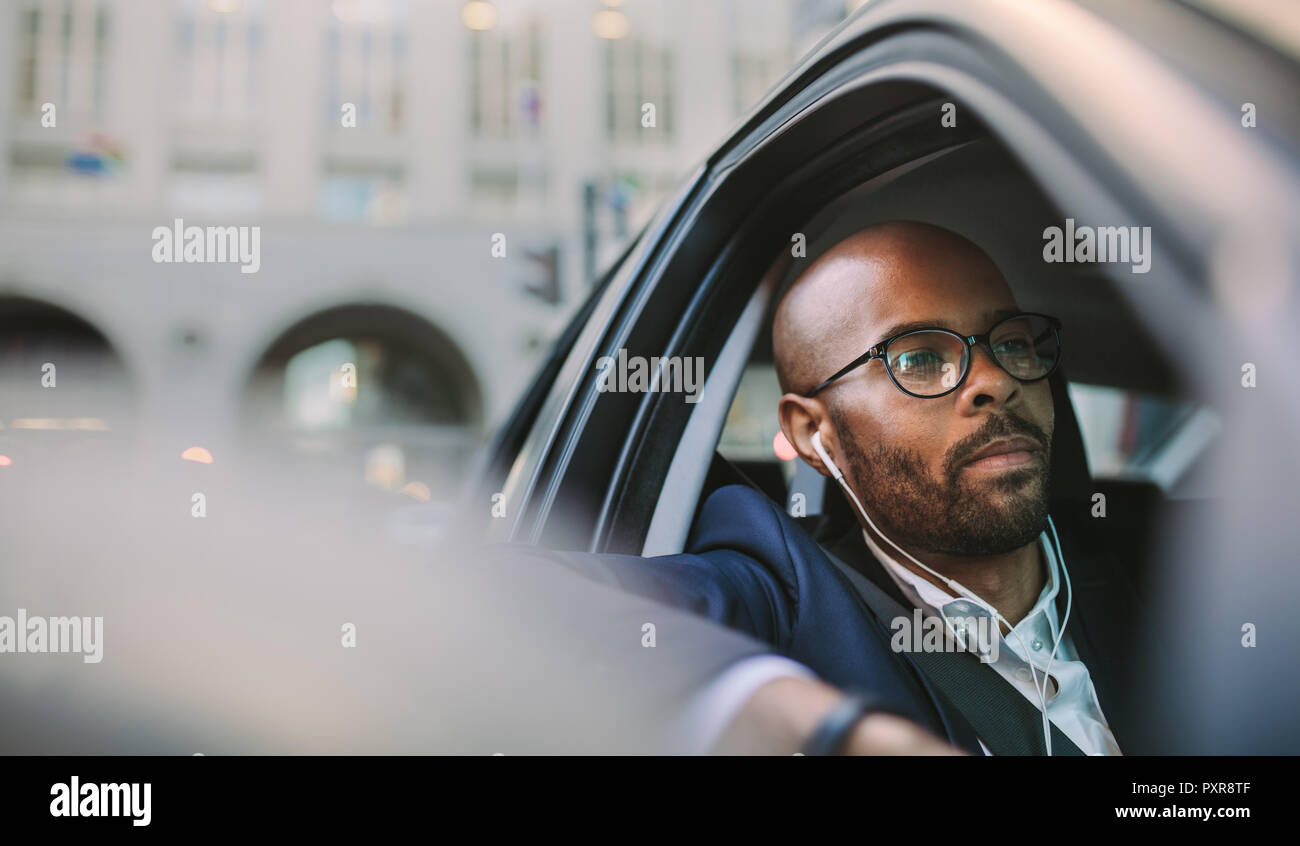 Businessman wearing earphones and listening musing while driving a car. African businessman being stuck in morning traffic. - Stock Image