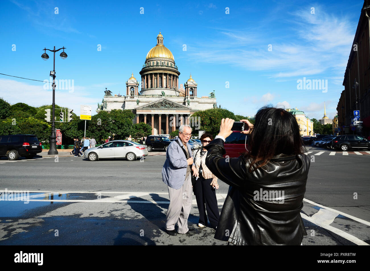 Tourists photographing in front of the Cathedral of St. Isaac. Saint Petersburg, Northwestern, Russia. - Stock Image