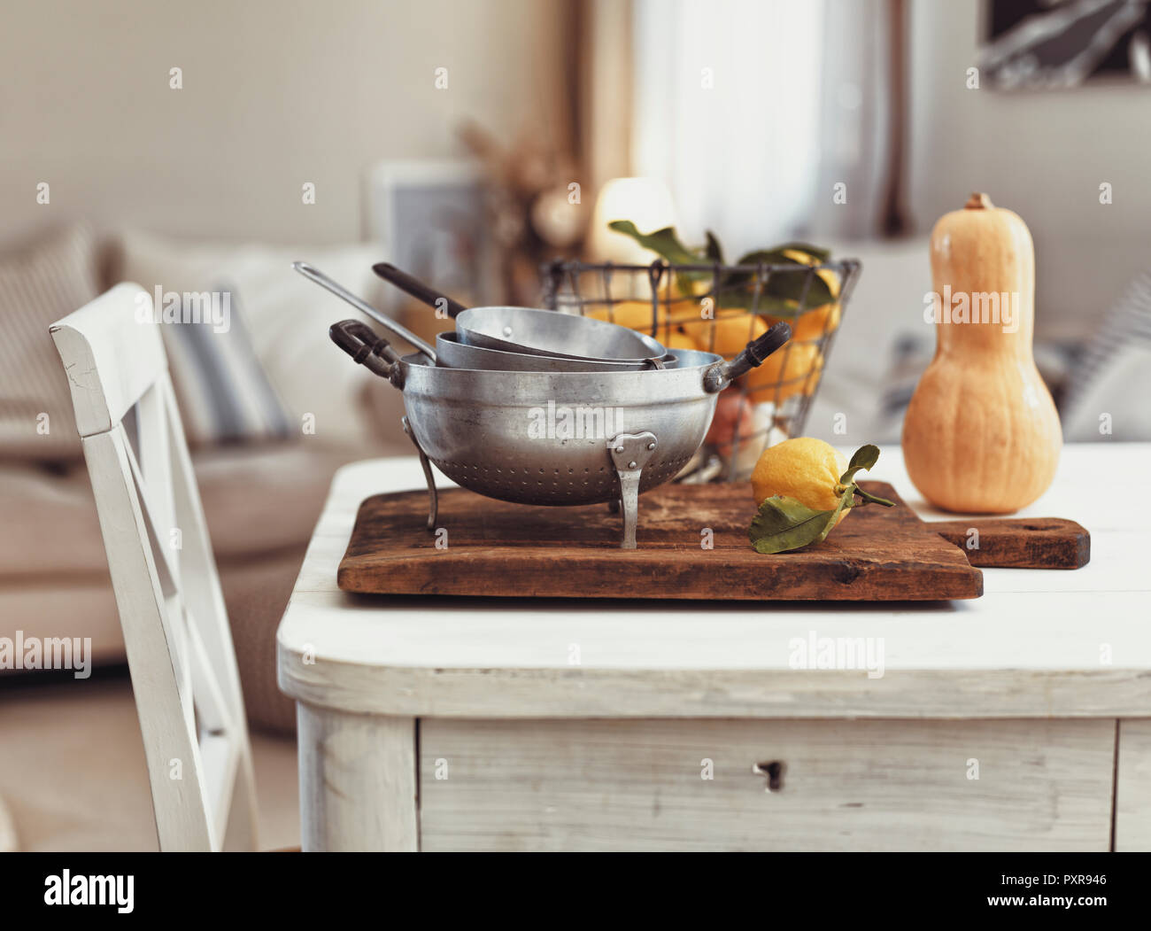 Nostalgic kitchen utensils and fruits on old wooden table - Stock Image