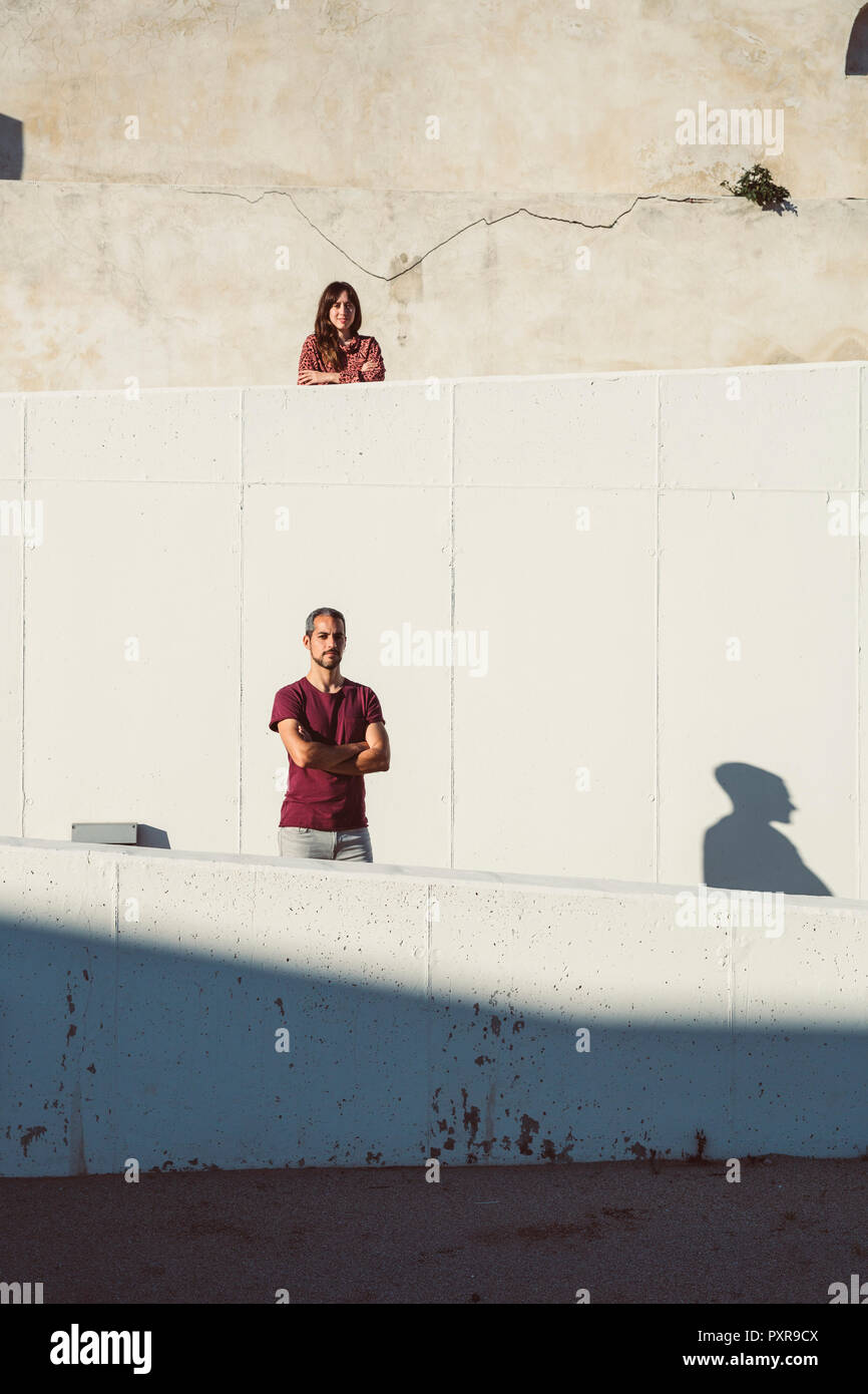 Man and woman standing on different levels of a wall, with arms crossed - Stock Image