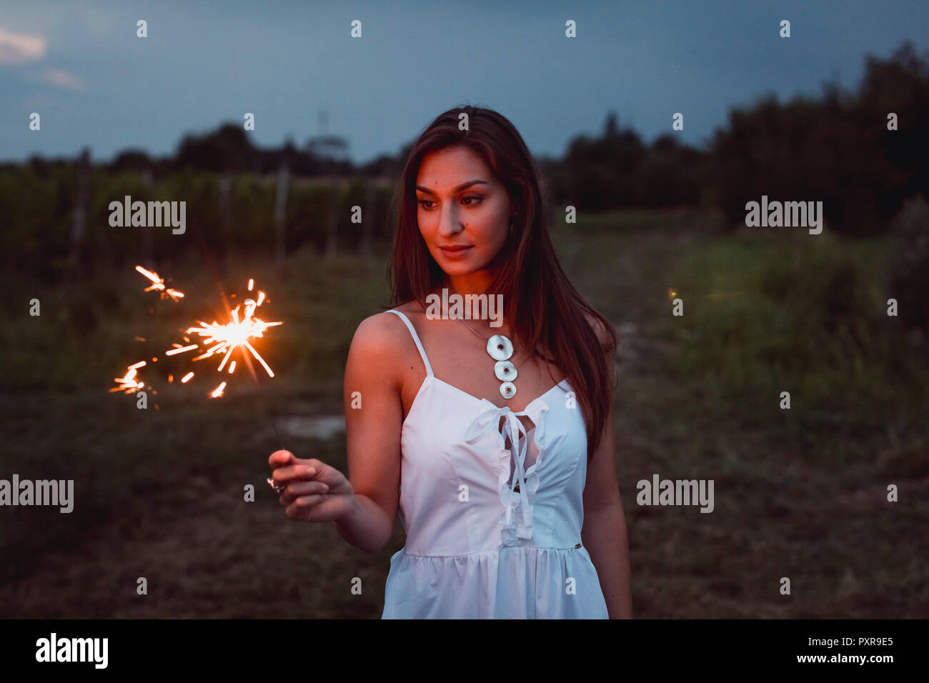 Young woman in nature, burning sparkler in the evening Stock Photo