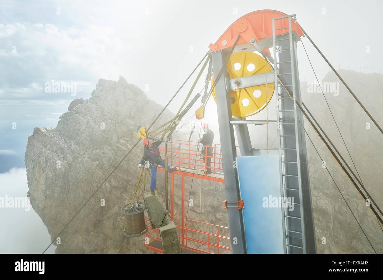 Germany, Bavaria, Garmisch-Partenkirchen, Zugspitze, installers working on goods cable lift Stock Photo